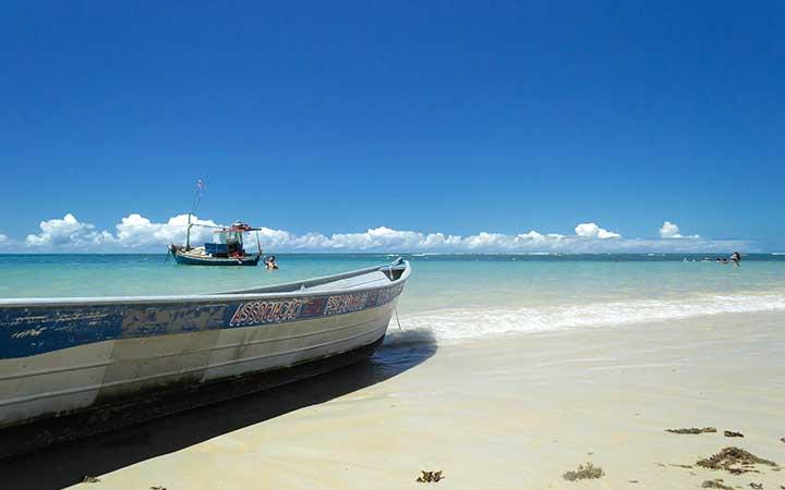 Barco na orla da praia de Trancoso