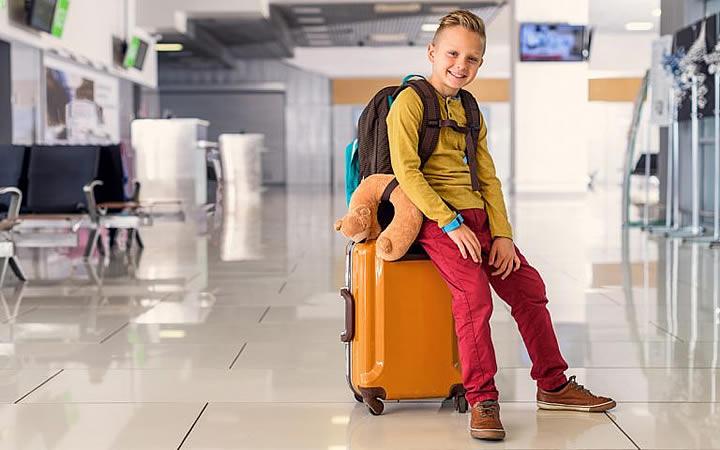 Criança sentada na mala
