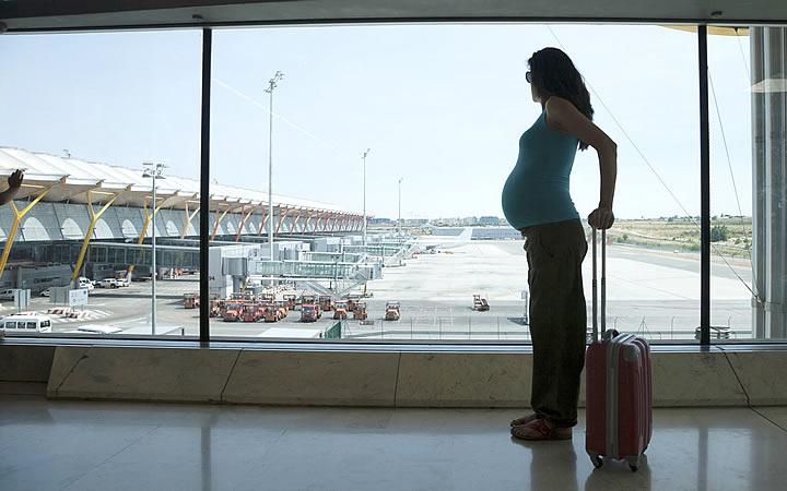 Grávida olhando o estacionamento dos aviões - grávidas podem viajar de avião