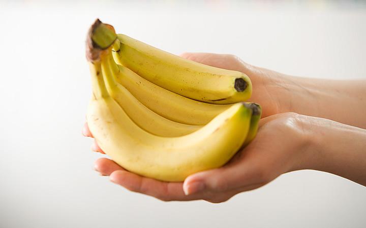 Pessoa segurando uma penca de banana