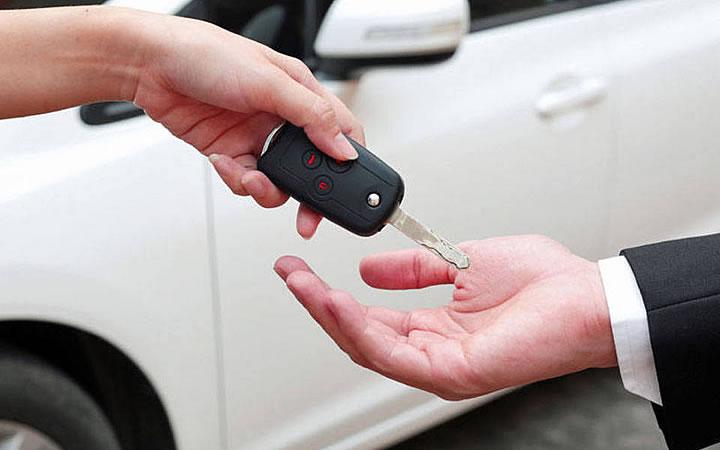 Alugar automóvel - Homem pegando a chave do carro