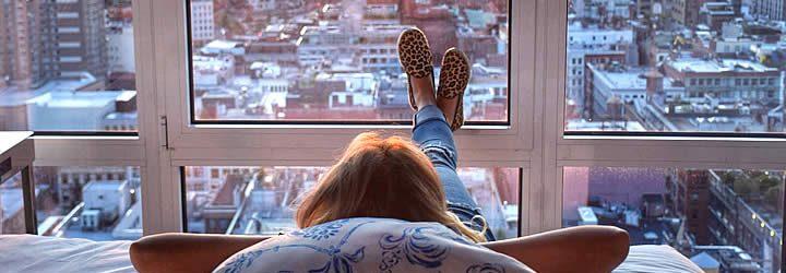 Mulher deitada uma cama de hotel observando Nova Iorque