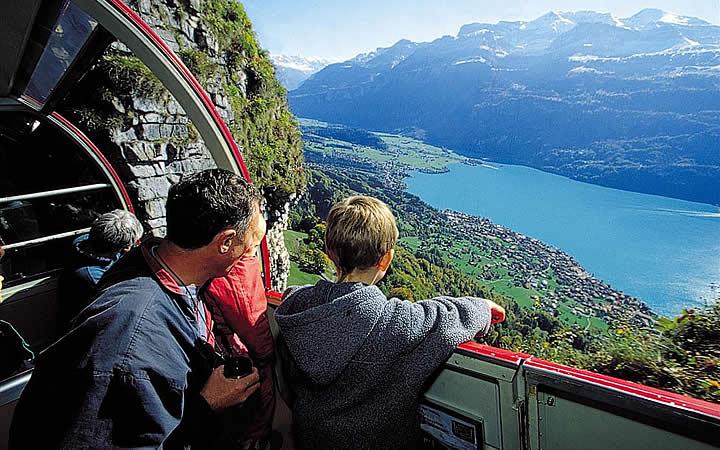 Pai com filho viajando de trem na Suíça