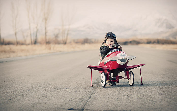 Bebê em avião de brinquedo