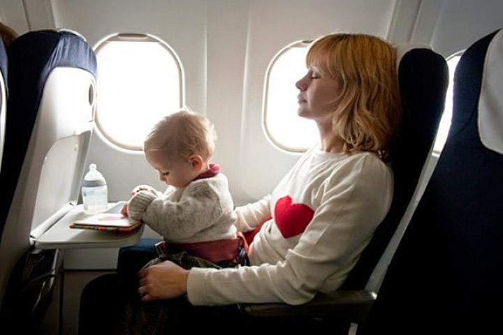 Bebê viajando de avião no colo da mãe