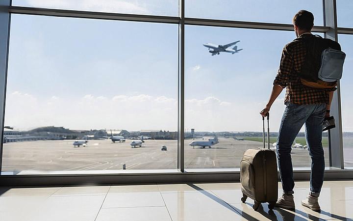 Pessoa em aeroporto vendo avião