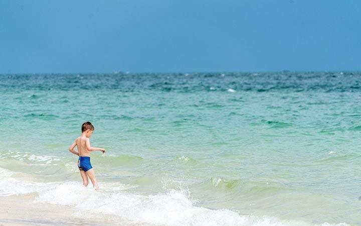 Criança na orla da praia