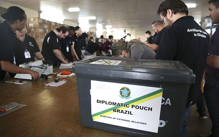 Equipe do TRE DF em uma mesa organizando os equipamentos para eleição