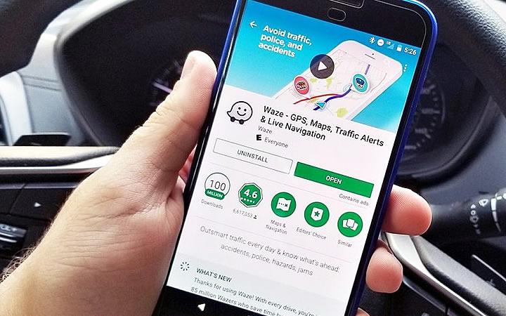 Pessoa em carro segurando smartphone na tela de instalação do aplicativo waze