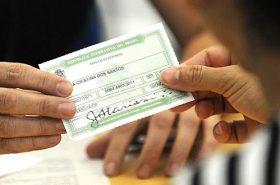 Pessoa entregando o título de eleitor - Justificar o voto no exterior