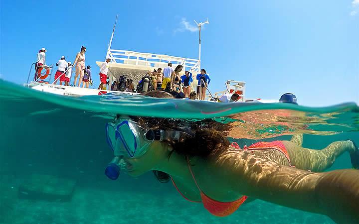 Pessoa fazendo mergulho próximo a uma lancha em Maracajaú