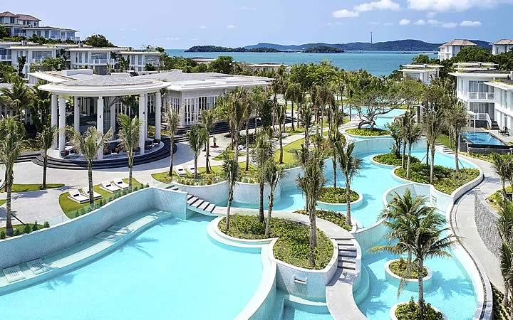 Piscinas com vários coqueiros por perto em um Resort