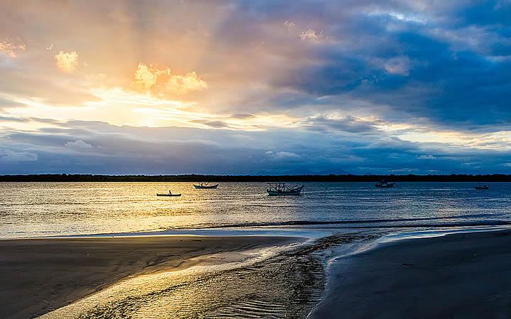 Amanhecer no Parque Nacional do Superagui com um barcos no mar