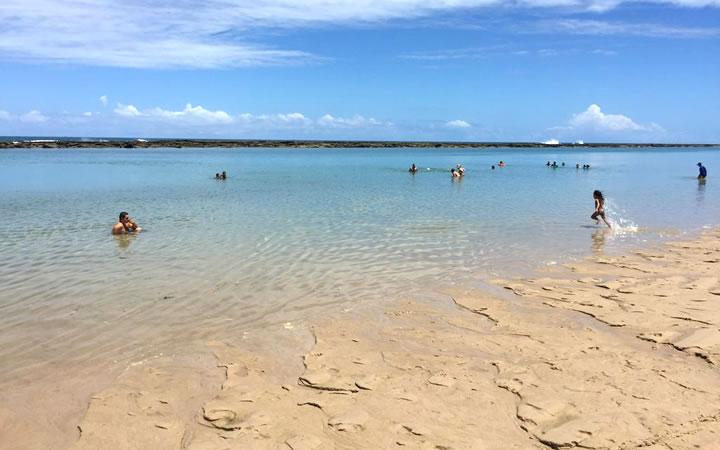 Criança correndo na praia em Barra de São Miguel