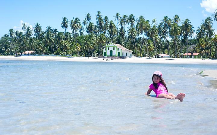 Criança deita na orla da Praia dos Carneiros