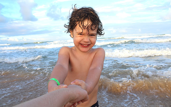 Criança sorrindo na Praia - Com pulseira de identificação