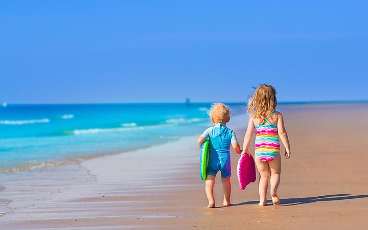 Crianças caminhando na orla da praia segurando uma prancha