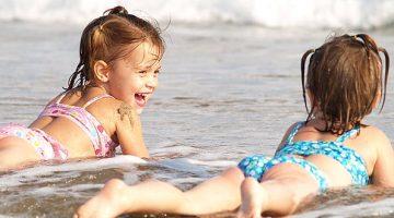 Duas crianças deitada na areia da praia
