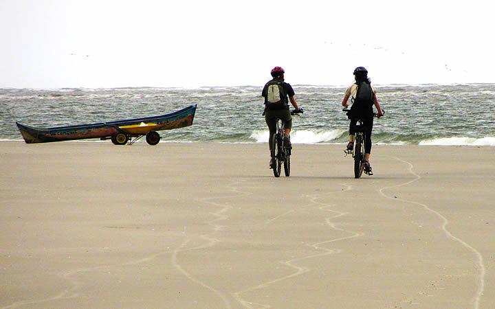 Duas pessoas pedalando na Praia deserta da Ilha de Superagui