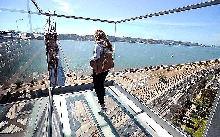 Mulher na plataforma suspensa de vidro em Cabo Girão