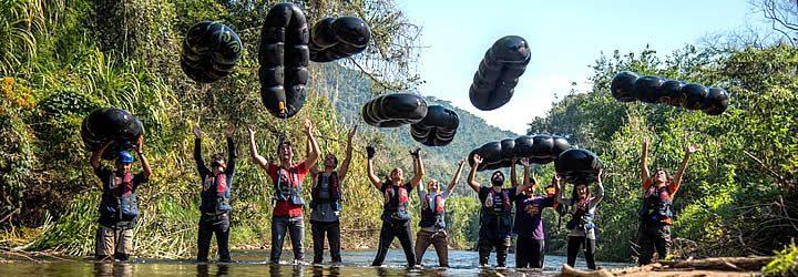 Pessoas em um rio jogando suas boias para cima
