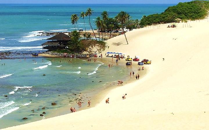 Pessoas na orla da Praia de Genipabu