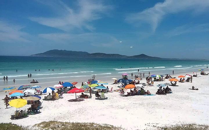 Pessoas sentadas tomando sol na Praia das Dunas em Cabo Frio