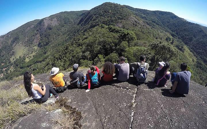 Grupo de pessoas no alto da pedra do forno