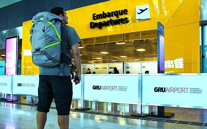 Homem em frente ao local de embarque no aeroporto