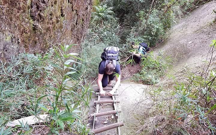 Mulher subindo escada na Trilha da Pedra Riscada