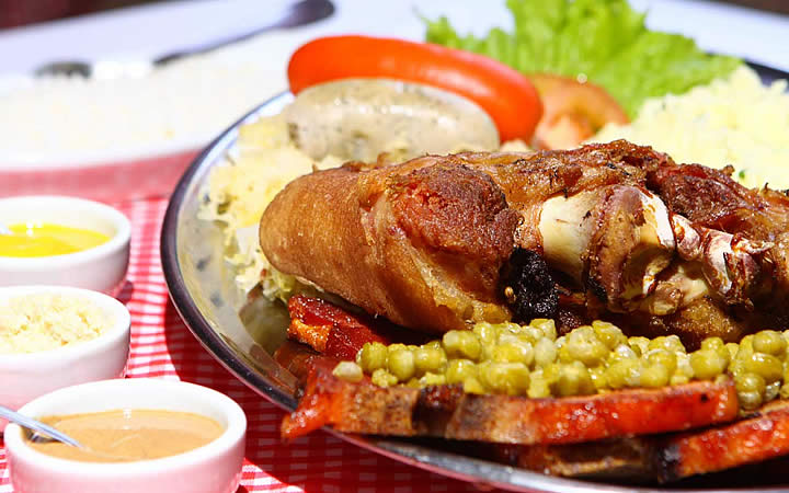 Prato de comida com frango, ervilha, arroz e molhos ao lado - Gastronomia de Pomerode