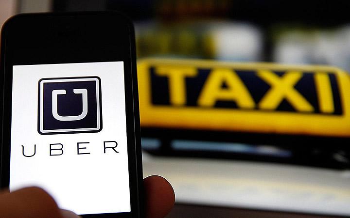 App do uber e painel do taxi ao fundo