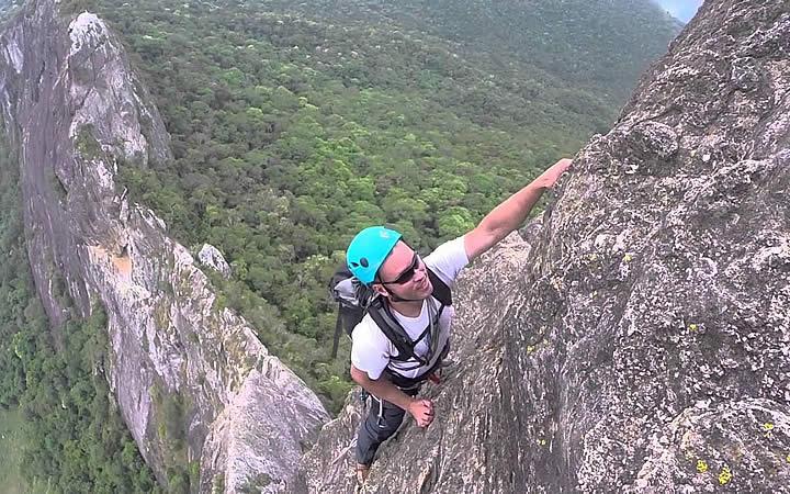 Homem escalando a pedra do Baú