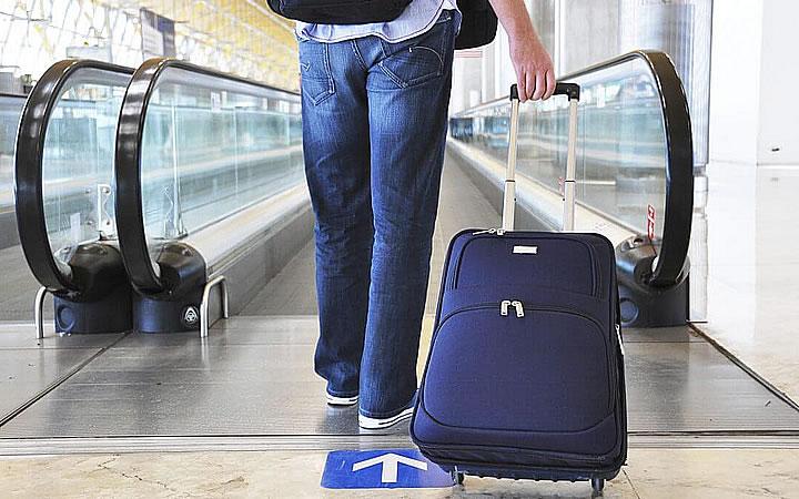 Homem segurando mala de viagem