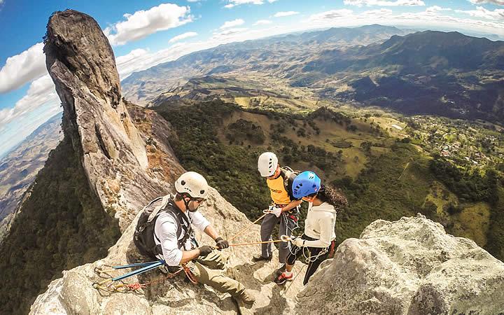 Instrutor de esporte de aventura com equipamentos de segurança no alto da pedra
