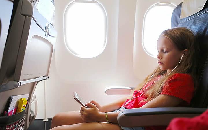 Menina ouvindo musica no avião