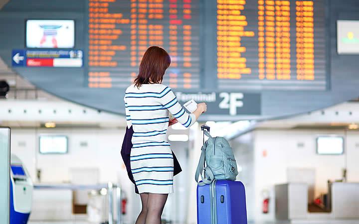 Mulher com bagagem conferindo documentos