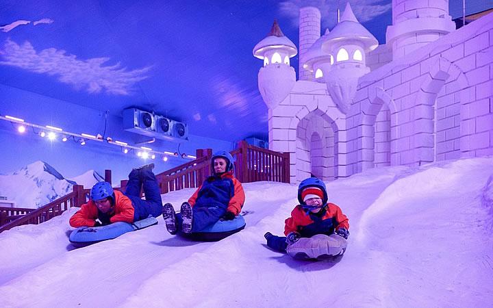Pessoas descendo a montanha de neve no parque Snowland
