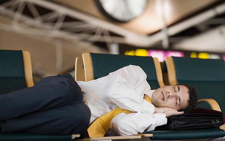 Homem dormindo nas cadeiras do aeroporto