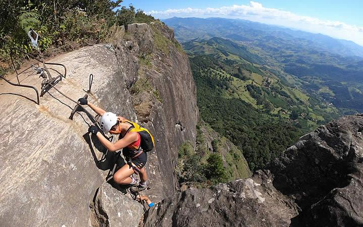 Homem escalando na trilha da Pedra do baú