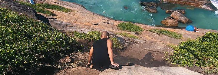 Homem tentando descer a trilha da praia do Secreto