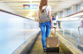 Menina puxando mala de viagem