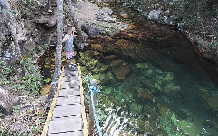 Menino próximo ao poço verde esmeralda na Cachoeira Loquinhas