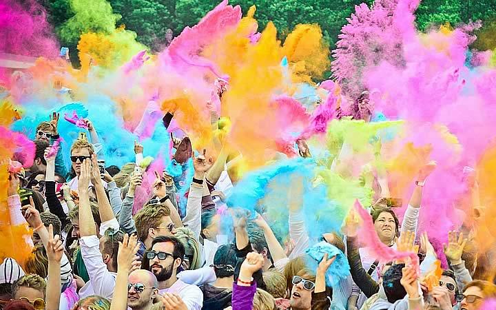 Pessoas jogando o pó colorido para cima no Holi Teen