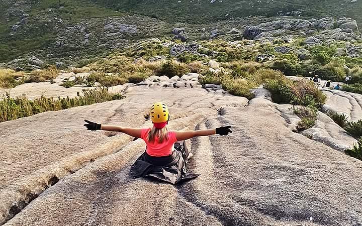 Mulher sentada no inicio da trilha para o Pico das Agulhas Negras