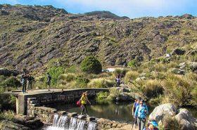 Pessoas atravessando o lago do Abrigo Rebouças - Pedra do Altar - Itatiaia