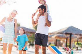 Família andando na praia - Viajar nas férias