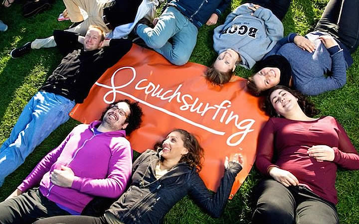 Pessoas deitada em cima da bandeira do Couchsurfing