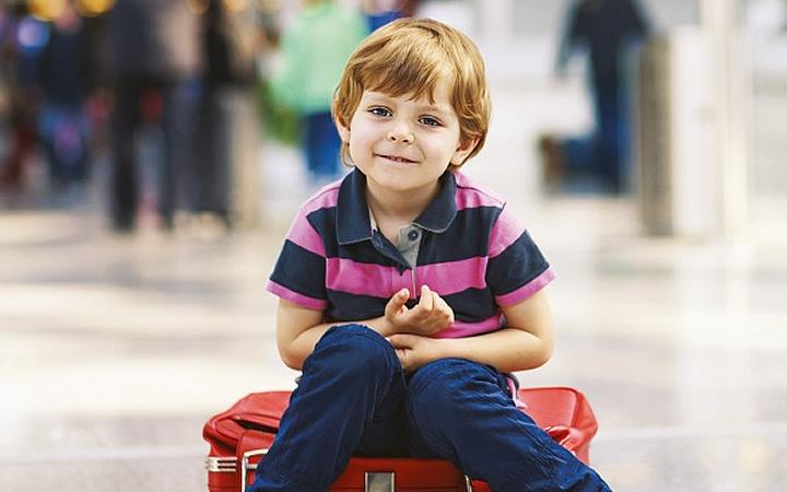 Criança sentada na mala de viagem