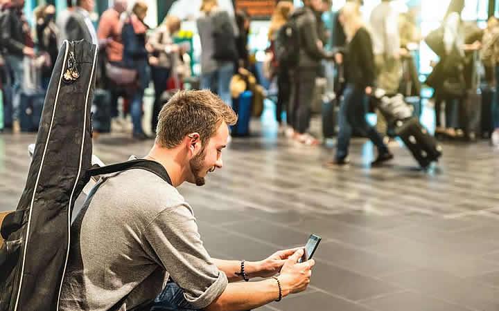 Homem com violão e mexendo no celular